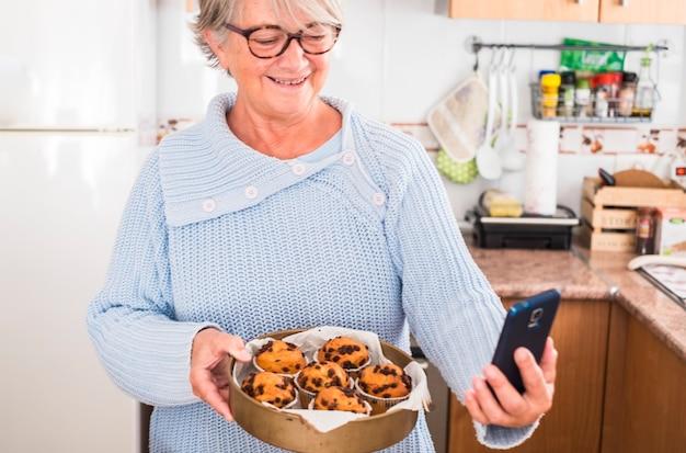 Vovó segurando um monte de muffins enquanto tira uma selfie na cozinha - mulher feliz e curtindo - usando óculos e sweather azul