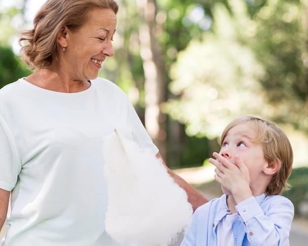 Vovó sorridente e criança com algodão doce