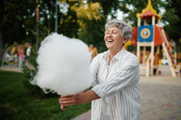 Vovó sorridente segurando algodão doce, parque de diversões
