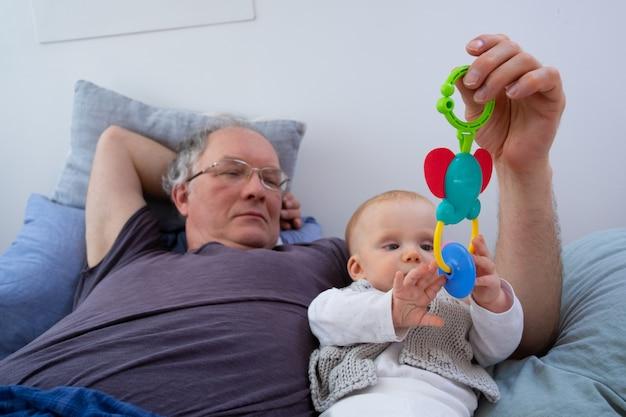 Vovô tranquilo, brincando com o bebê, segurando o brinquedo de chocalho