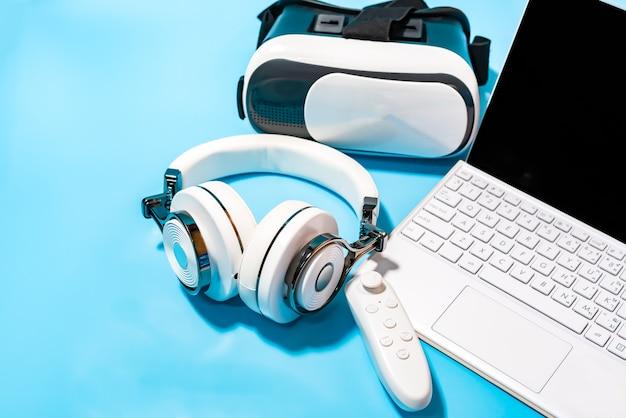 Vr, fone de ouvido, laptop sobre fundo azul. conceito para vr, jogo, simular e tecnologia.