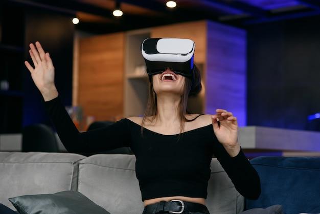 Vr. menina milenar animada usando fone de ouvido de realidade virtual jogando videogame interior. foco seletivo