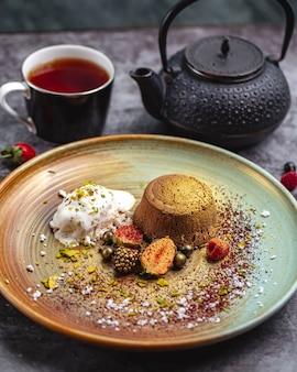 Vulcão de chocolate tingido de ouro servido com sorvete de baunilha e frutas e chá