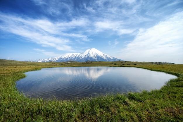 Vulcão e lago com reflexo na água na rússia em kamchatka
