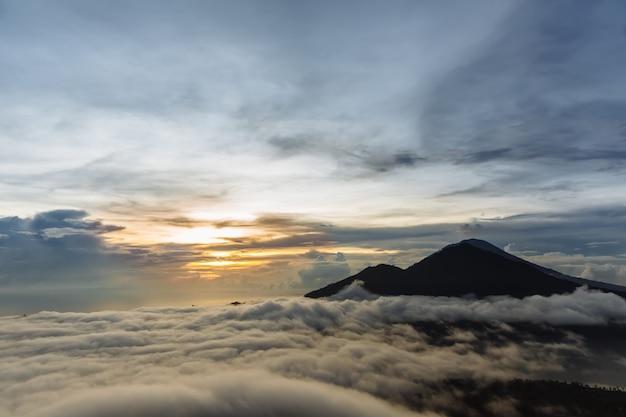 Vulcão indonésio ativo batur na ilha tropical bali. indonésia. serenidade do nascer do sol do vulcão batur. céu do amanhecer de manhã na montanha. serenidade da paisagem de montanha, conceito de viagens