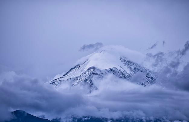 Vulcão mexicano coberto de nuvens e neve