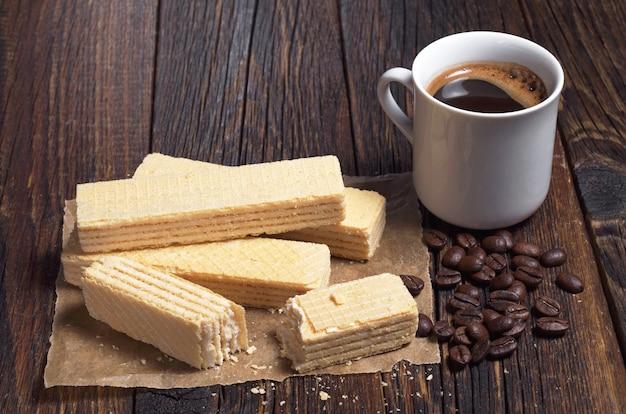 Wafers deliciosos e uma xícara de café quente na mesa de madeira escura