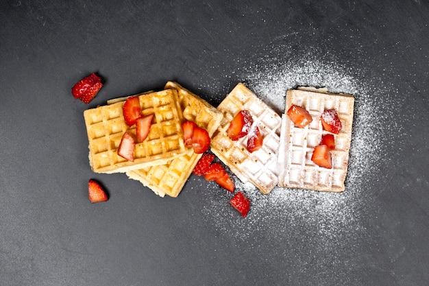 Waffers de bélgica com morangos e pó do açúcar no fundo preto da placa.