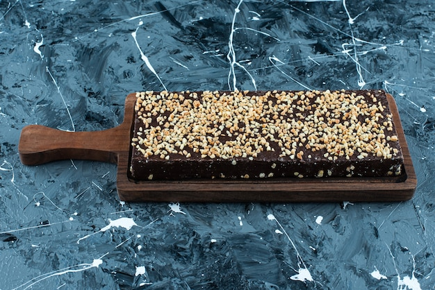 Waffle coberto de chocolate em uma placa, na mesa azul.