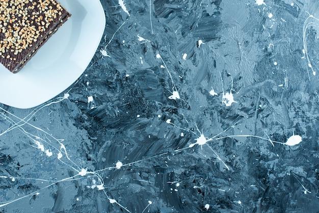 Waffle coberto de chocolate num prato, na mesa azul.