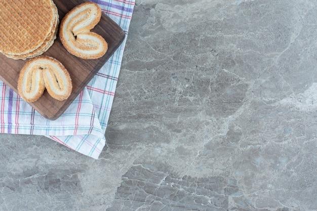Waffle com biscoito na placa de madeira sobre fundo cinza.