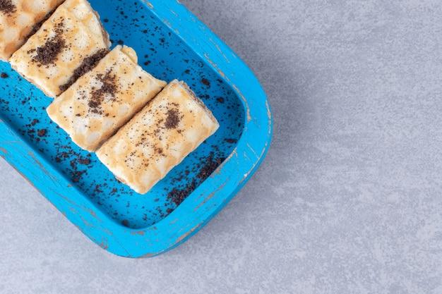 Waffle com recheio de chocolate rola em uma travessa azul sobre mármore