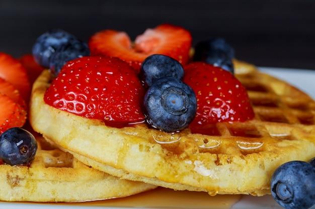 Waffle de café da manhã com blueberries frescas, morangos e xarope de bordo