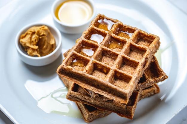 Waffle de chocolate com mel em uma placa de vista lateral