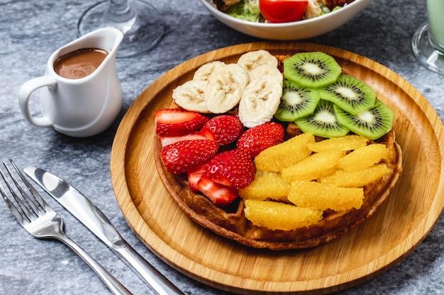Waffle de vista lateral com kiwi banana morango laranja e chocolate em cima da mesa