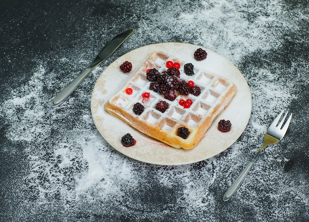 Waffle delicioso em um prato com amoras, vista de alto ângulo garfo no escuro