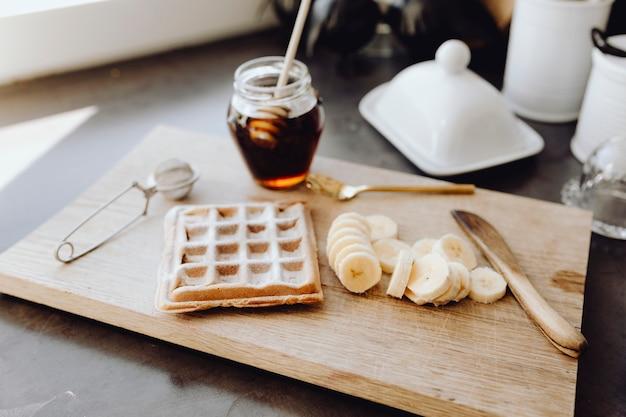Waffle e fatias de banana em uma bandeja de madeira ao lado de um pote de mel