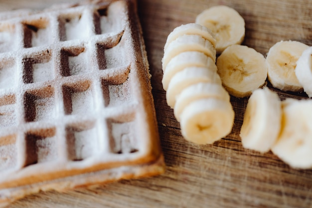Waffle e fatias de banana em uma bandeja de madeira