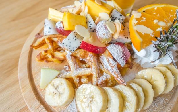 Waffle e frutas com gelado na tabela.