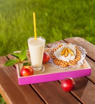 Waffle e milkshake na mesa de madeira no jardim