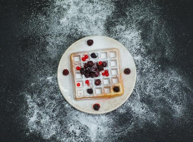 Waffle em um prato com amoras vista superior no escuro