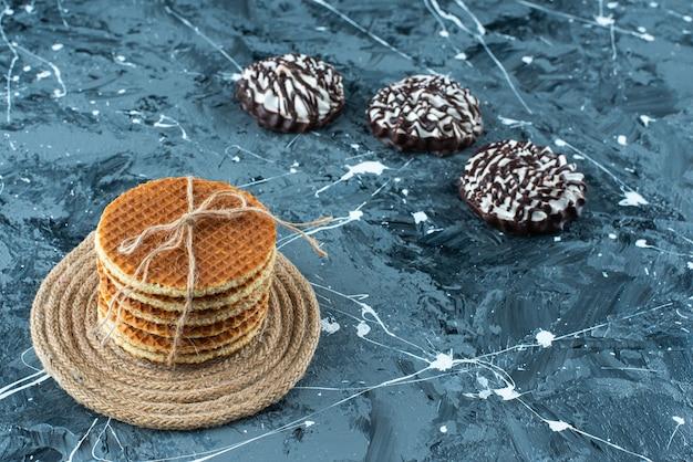 Waffle em um tripé ao lado do biscoito de chocolate, na mesa azul.