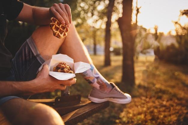 Waffle fresco segurando nas mãos, refeição americana para viagem. granulação do filme, imagem tonificada