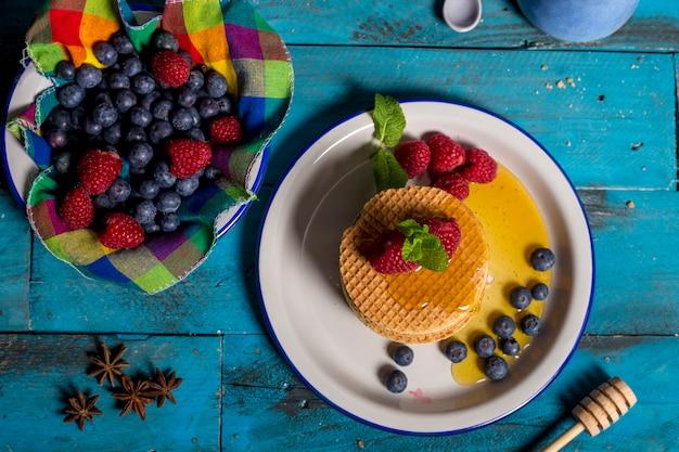 Waffle holandês café da manhã com framboesa, mirtilo e mel sobre fundo azul de madeira. imagem isolada tiro aéreo. conceito de pequeno-almoço.