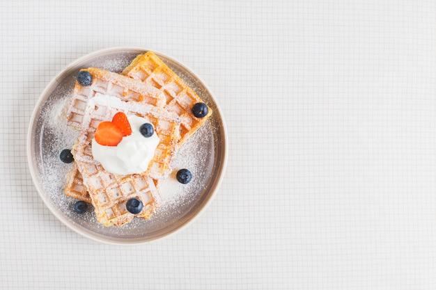 Waffle marrom dourado coberto com morangos fatiados; mirtilos e chantilly na placa