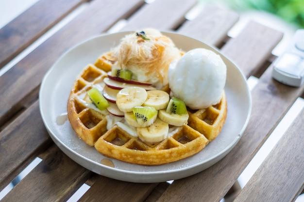Waffle marrom dourado coberto com sorvete de frutas fatiado e chantilly e algodão doce