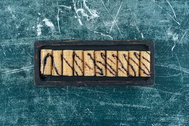 Waffle roll em uma placa, na mesa azul.