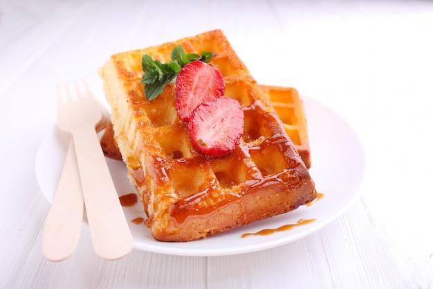 Waffles bávaros servidos com caramelo e morango na chapa branca
