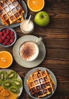 Waffles belgas, café, iogurte, frutas e bagas em um fundo de madeira, conceito de café da manhã.