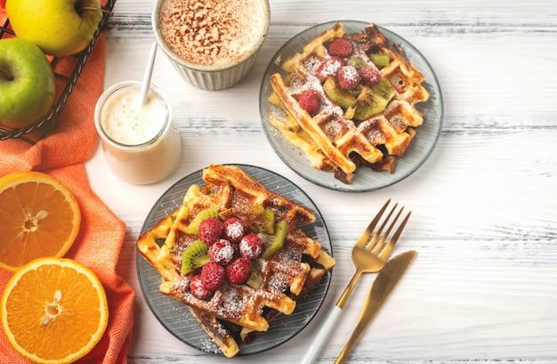 Waffles belgas, café, iogurte, frutas em um fundo de madeira branco, conceito de café da manhã.