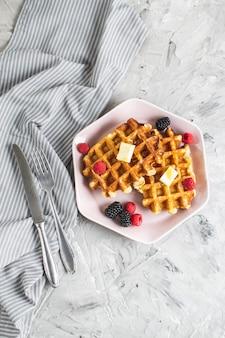 Waffles belgas caseiros com manteiga mel bagas framboesas amoras mesa toalha de cozinha prato rosa café da manhã
