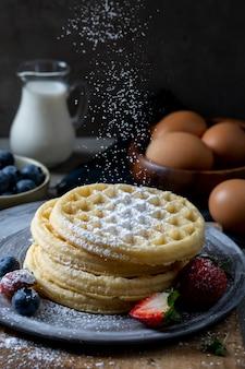 Waffles belgas caseiros com mirtilo e morango, derramando cobertura de açúcar de confeiteiro.