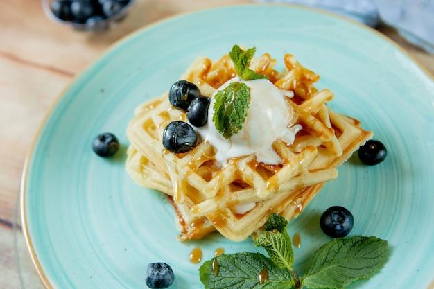 Waffles belgas clássicos caseiros cozidos frescos, cobertos com sorvete, mirtilos frescos e hortelã