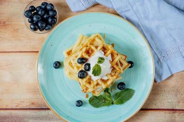 Waffles belgas clássicos caseiros recém-assados cobertos com sorvete, mirtilos frescos e hortelã