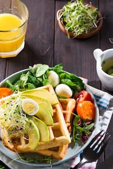 Waffles belgas com abacate, ovos, micro verde e tomate com suco de laranja na mesa de mármore
