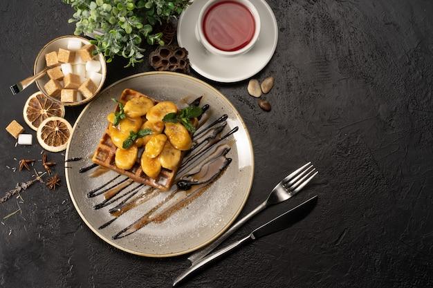 Waffles belgas com banana, chocolate e caramelo, decorados com folhas de hortelã. sobremesa tradicional para chá ou café.