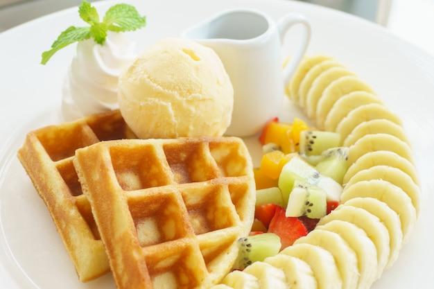 Waffles belgas com chocolate, bananas e morangos, com molho de xarope.