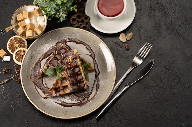 Waffles belgas com chocolate decorado com folhas de hortelã. uma bela sobremesa quente para chá ou café.