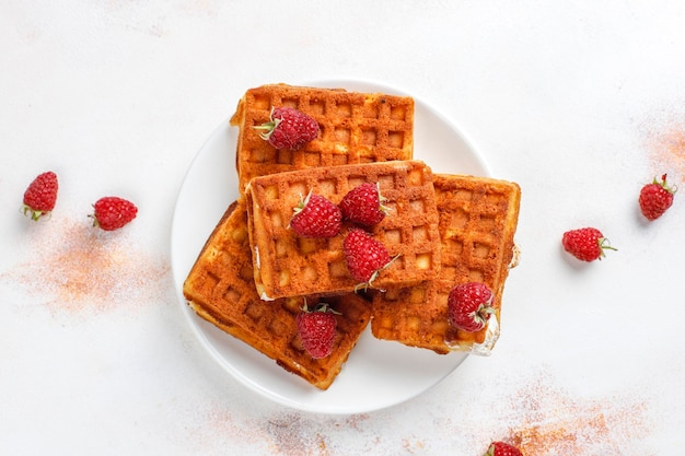 Waffles belgas com creme e framboesas frescas.