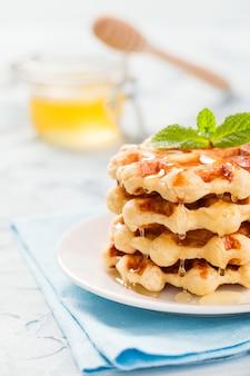 Waffles belgas com folhas de mel e hortelã sobre fundo azul pastel.