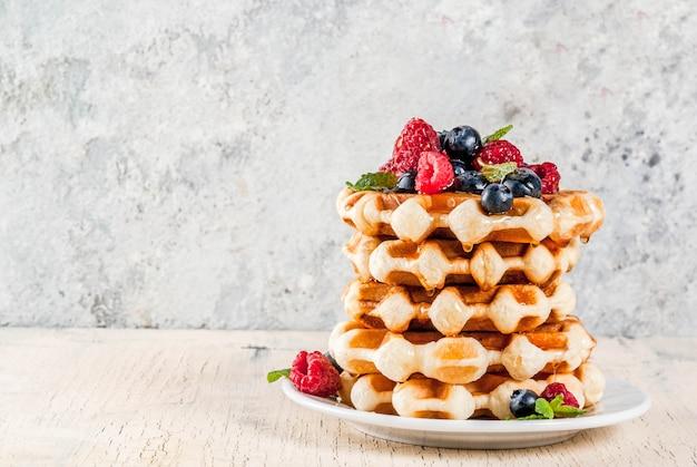 Waffles belgas com framboesas, mirtilos e calda