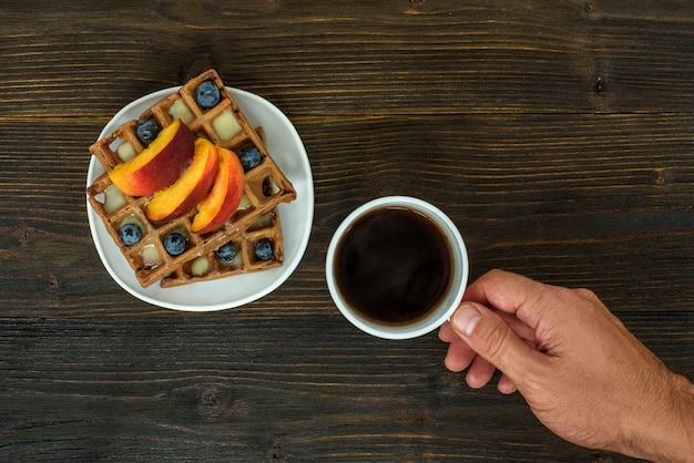 Waffles belgas com frutas e bagas. mão masculina com uma xícara de café. vista do topo
