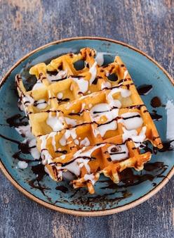 Waffles belgas com frutas frescas e molho de chocolate.