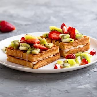 Waffles belgas com frutas morangos e kiwi na chapa branca na mesa de concreto