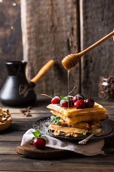 Waffles belgas com mel. cerejas grãos de café em frasco de vidro.