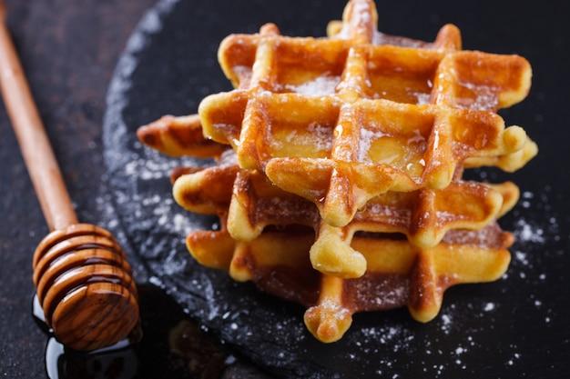 Waffles belgas com mel em um fundo preto.